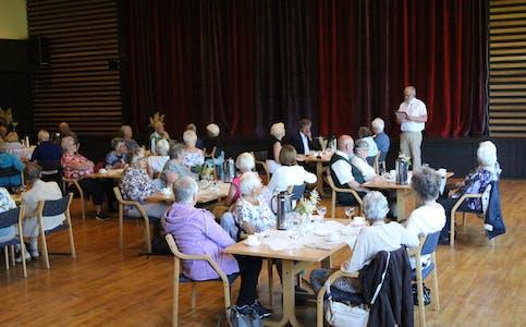LESESTUND: Ein ikkje ukjend, tidlegare lokalavisredaktør underheldt med opplesing ved sida av mat, prat og fleire allsongar for dei 45 deltakarane i Volda Pensjonistlag sin «Middag for eldre»-tur.