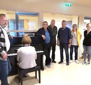 PIANO: No vert det mykje fin pianomusikk på avdeling 3 framover. Aslaug Gusdal spelar ein melodi med sonen Jan Åge til venstre. På andre sida av pianoet står Bjarne Kløvning, Magne Berge, Kjellbjørn Nystøyl, Jorunn Nystøyl frå Trivsel for eldre og Lena Beate Eikeset frå VHO som har stått for planlegging.