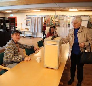 FERDIG: Arnhild Honningsvåg var ein av dei første til å legge stemmesetelen i urna på Fiskå. Håkon Brudevik og dei andre valfunksjonerane er på plass og ordnar med hjelp og registrering.